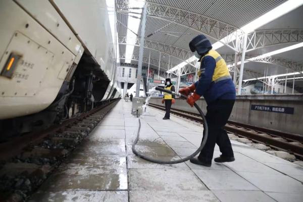 图为极寒天气下,吉林站上水员高嵩反复将上冻的水管在地面摔打,直到把解冻的积冰摔出,再继续上水作业。.jpg