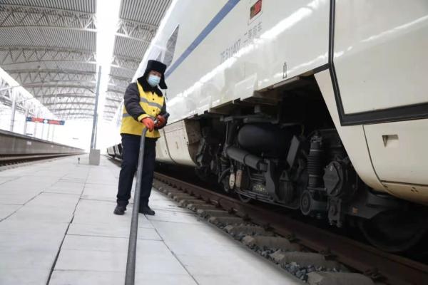 图为吉林站上水员在阴冷的道沟里来来回回拖拽着水管奔跑,对每节列车进行注水。.jpg