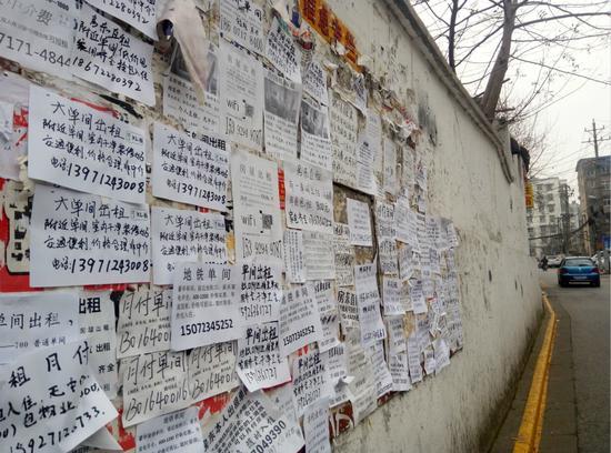 2017年1月3日,武汉一商圈附近小巷里,大量房屋出租小广告贴满围墙图片
